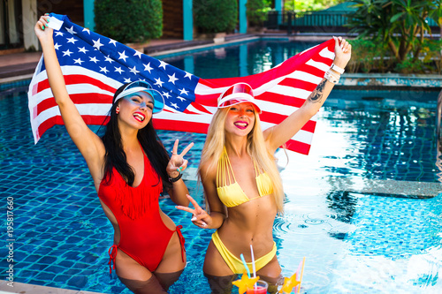41f60658670 two beautiful sexy girls in a bikini in a pool in sunshades holding an American  flag in their hands