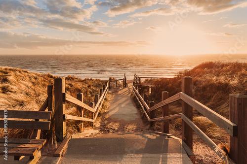 Foto auf Gartenposter Strand Holztreppe mit Blick auf das Meer beim Sonnenuntergang