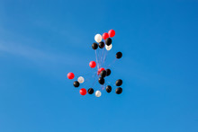 Red White Black Balloons Floating Away Against A Blue Sky