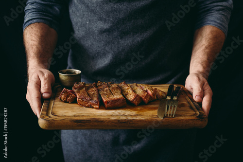 Papiers peints Steakhouse Man holding juicy grilled beef steak with spices on cutting board