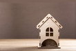 Home improvement and building concept - Wooden model house on a wooden desk