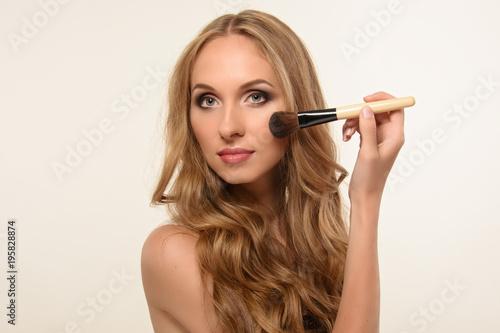Fotografía  Beautiful young girl is applying makeup. Clean skin.