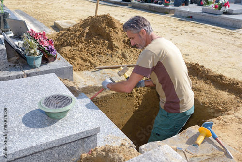 Spoed Foto op Canvas Begraafplaats Man in grave using hammer and chisel