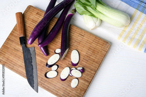 japanese eggplant on wooden board with knife and pak choi salad