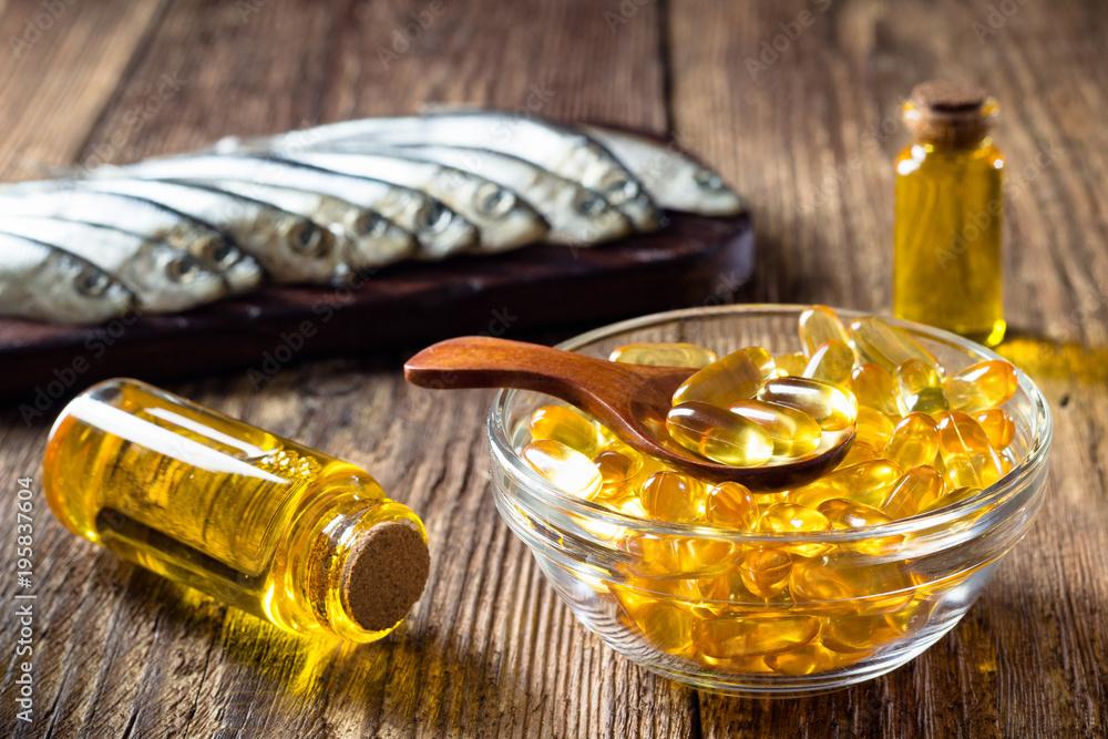 Fototapeta Fish oil capsules on wooden background, vitamin D supplement