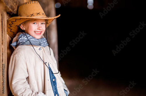 a little girl in a cowboy hat stands near the wall of a barn - Buy ... e715eab98a92