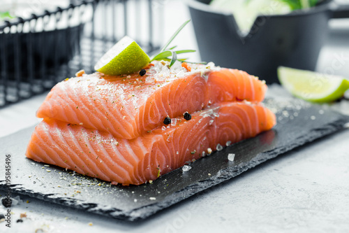 Valokuvatapetti Two pieces of raw salmon fillet with fresh herb rosemary, spices and olive oil o