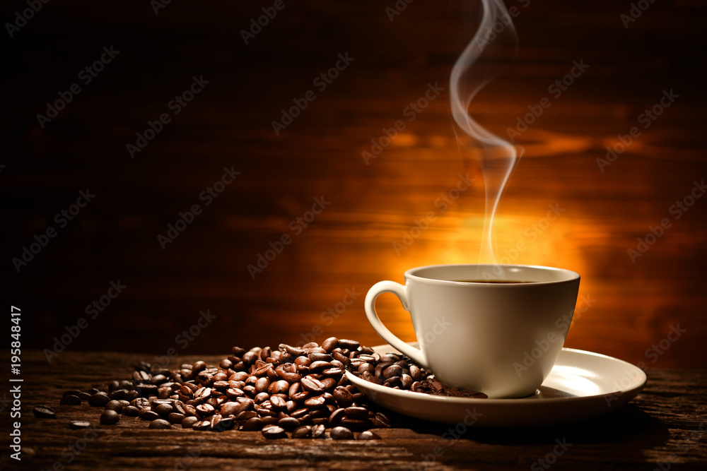 Cup of coffee with smoke and coffee beans on old wooden background