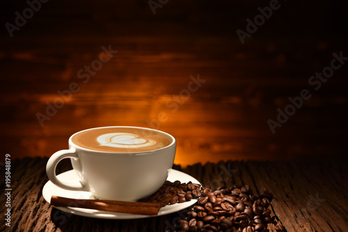 Poster Cafe Cup of coffee latte and coffee beans on old wooden background