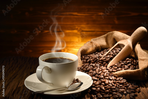 Wall Murals Cafe Cup of coffee with smoke and coffee beans on old wooden background