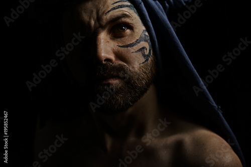 Photo  tattoo on the face,  male portrait in the form of an assassin, cosplay,  tattooe