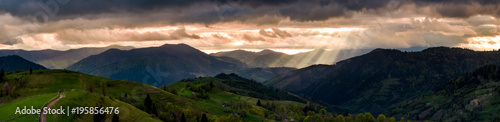 Photo sur Toile Saumon panorama of mountainous countryside at sunset. country road through rolling hills in to the distance. heavy clouds over the ridge. beams of lite from the heaven. beautiful and mysterious landscape