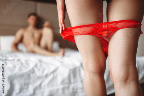Female legs with red panties down in front of man
