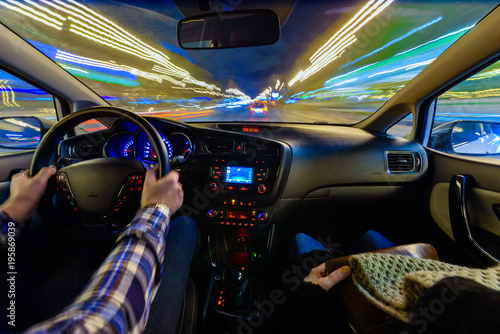 Fotografering  Driving in night scenery, hands on steering wheel, night rain time