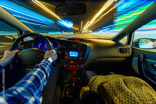 Fotografering  Driving in night scenery, hands on steering wheel, night rain time