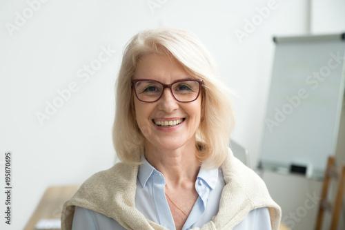 Smiling attractive senior businesswoman wearing glasses head shot, happy aged te Fototapeta