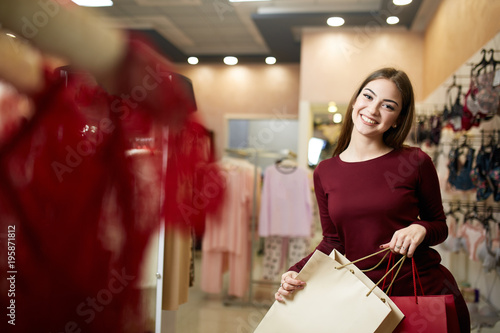 Smiling woman carrying some shopping bags with lingerie store showcase on  the background. Pretty smiling caucasian girl with purhaces in underwear  shop. f7d0401a1
