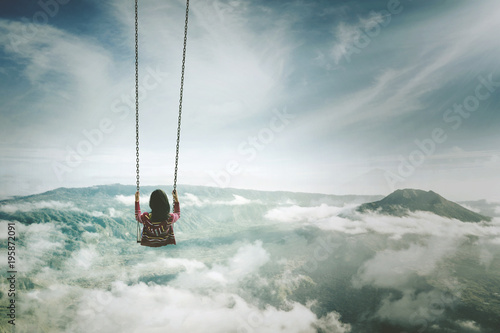 Young woman playing with swing above mountain