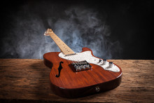 Vintage Electric Guitar On A Wood Raw Table. Musical Instrument. Black Background With Smoke