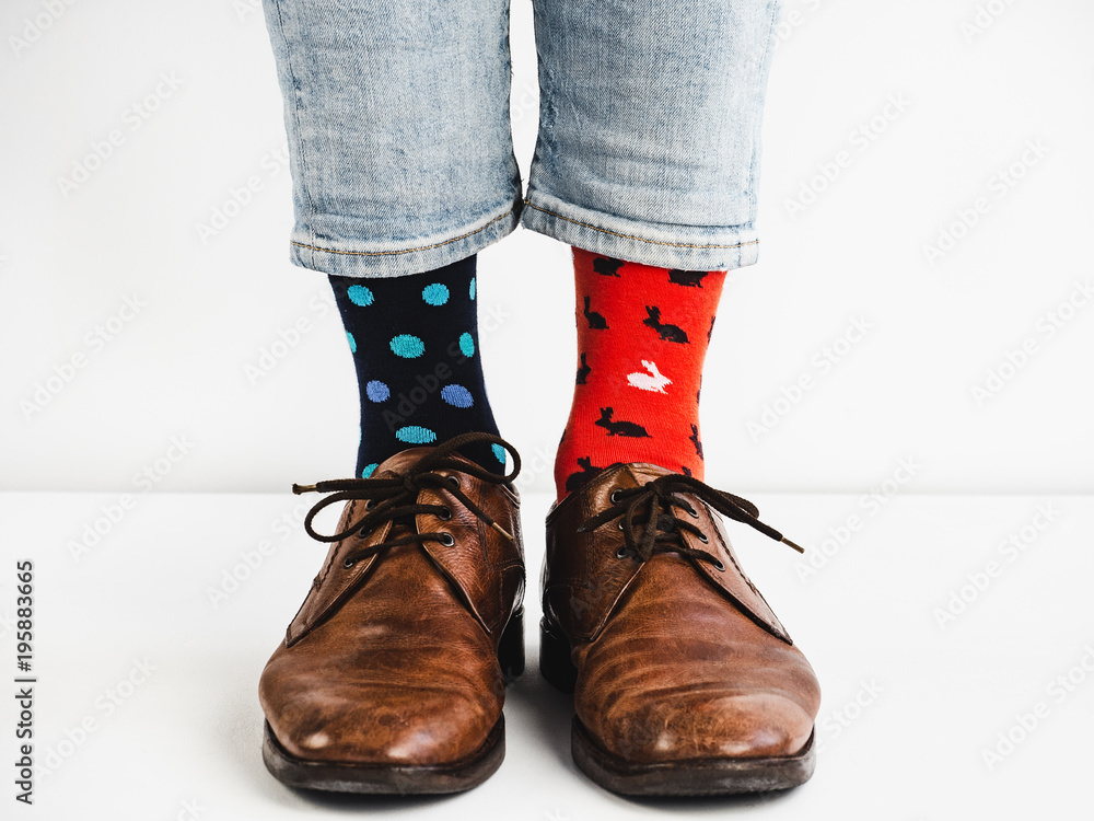 Fototapeta Male legs in bright, colorful socks and stylish, vintage shoes on a white background. Lifestyle, fashion, fun