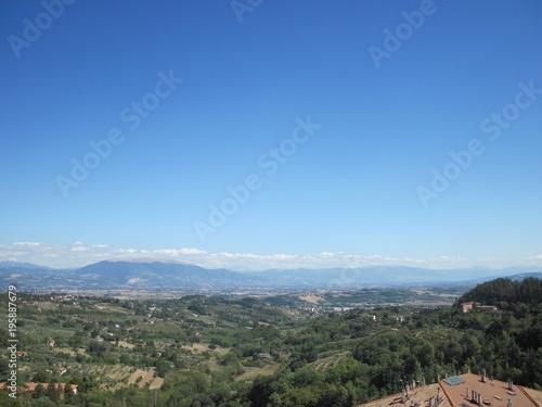 Fotografia  Pianura coltivata con alberi case colline