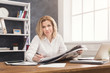 Smiling businesswoman reading newspaper at office desktop