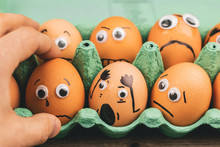 Fun Concept: Raw Eggs With Googly Eyes And Drawn Features Are In Shock While Sit In A Green Carton Box And Are Being Picked Up By A Hand