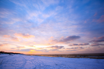 a beach under snow and a cold, ice-covered sea during sunset