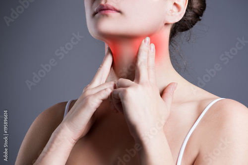 Fotografie, Obraz  Sore throat, woman with pain in neck, gray background
