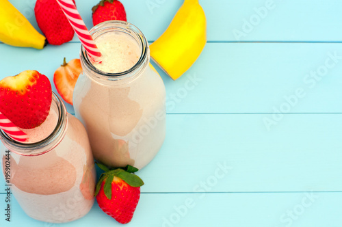 Fresh strawberry and banana milkshake on a turquoise wooden background (copy space)