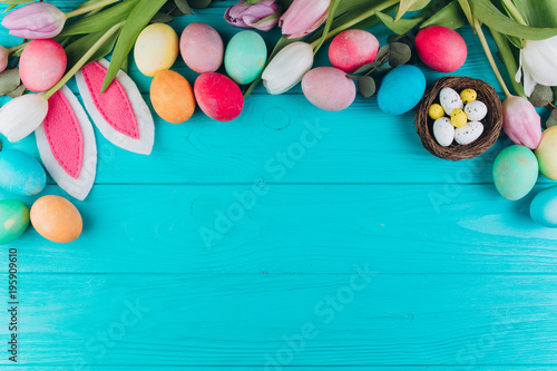 Easter composition with colored eggs, rabbit ears, nest and tulips on a blue wooden background.