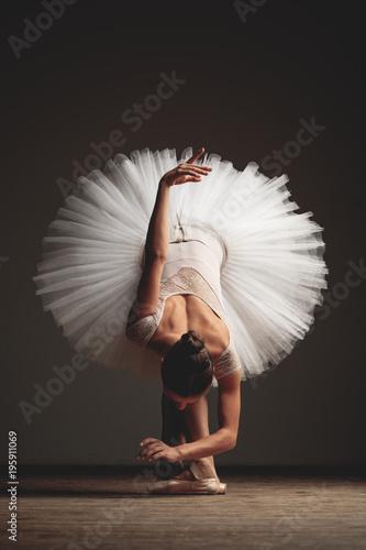 Foto Young beautiful ballerina is posing in studio