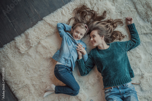 Fotografie, Obraz Smiling mother with her daughter in the room on the carpet