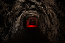 Infinite Tunnel With An Ominous Red Backlight Through The Rock