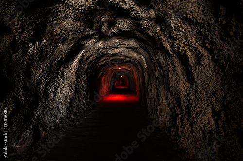 Slika na platnu Infinite tunnel with an ominous red backlight through the rock