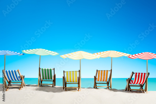Multi-colored sun loungers with umbrellas on the sandy beach Wallpaper Mural