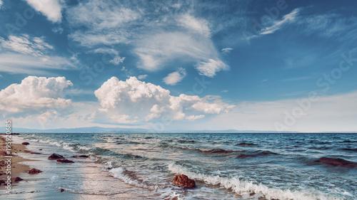 Obraz na płótnie Krajobraz piasek i skalisty brzeg. Piękny chmurny seascape przy zmierzchem i zamazaną ruch wodą.