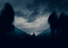 Long Exposure Of Pedestrians At London, England, UK Millenium Bridge With St. Paul's Cathedral In Background - Dystopia Dark Post-apocalyptic Fine Art Concept.