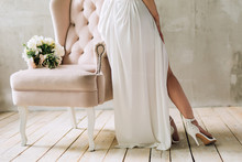 Legs Of The Bride In White Shoes And A Dress That Stands Near The Pink Chair On Which Lies A Wedding Bouquet On The Background Of A Gray Wall