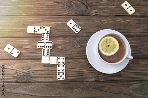 Foto op Plexiglas Chocolade a cup of tea with lemon, a domino on the background of a wooden table. Board games. leisure.