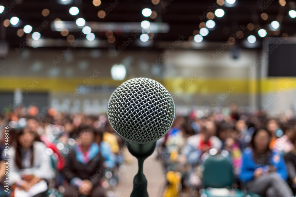 Fototapeta Microphone over the Abstract blurred photo of conference hall or seminar room in Exhibition Center background with Speakers on the stage and attendee background, Business meeting and education concept