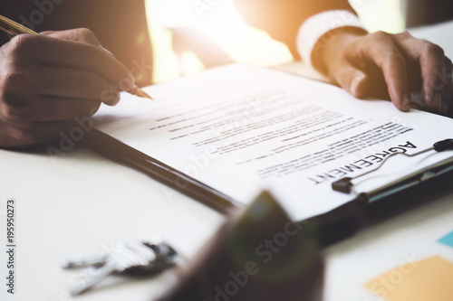 Fototapety, obrazy: Close up of Businessman pointing and signing agreement contract for buying house. Bank manager and real estate concept.