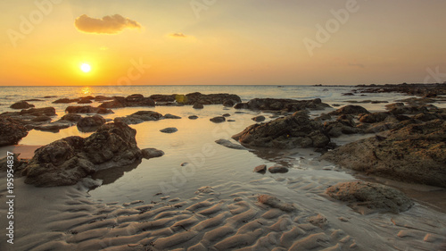 Fotografia Beach in golden sunset light during low tide showing sand formations and rocks not covered by the sea