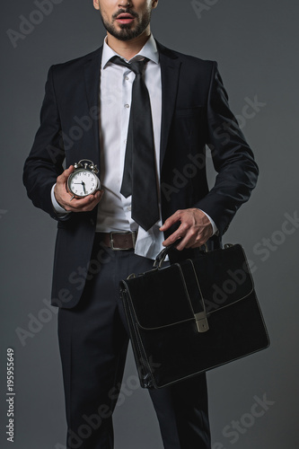 Fotografie, Obraz  Shocked young bearded man in business suit holding in hands snooze and brief-bag