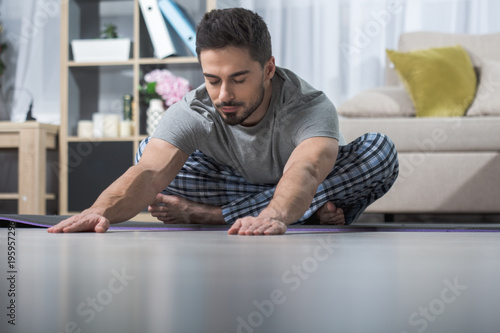 Foto op Aluminium Ontspanning Carefree attractive guy sitting in lotus position and stretching his arms forward on floor