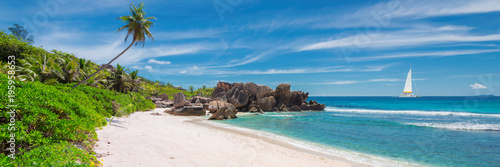 Fototapeta Sailing boat in the turquoise sea and sandy beach with palm trees and beautiful rocks on Seychelles. obraz