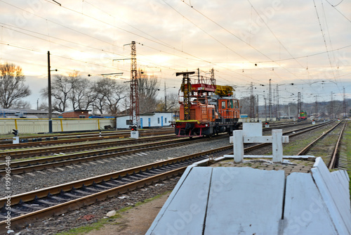Fototapeta Railway station against beautiful sky at sunset. Industrial landscape with railroad, colorful cloudy blue sky. Railway sleepers. Railway junction. Heavy industry. Cargo shipping. Travel background obraz na płótnie