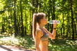 Fitness beautiful woman drinking water and sweating after exercising on summer hot day in park. Female athlete after work out.