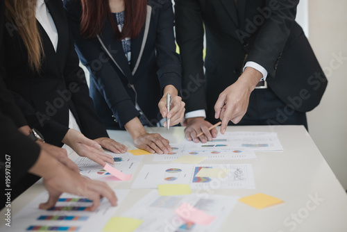 Fototapety, obrazy: Group Asian Young Businessmen and woman discussing on stockmarket charts at office desk, they are business analyzing. used laptop in the work. brainstorming, teamwork, meeting concept.