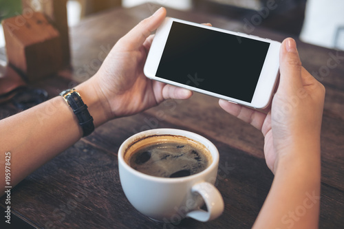 Fotografiet  Mockup image of hands holding white mobile phone with blank black screen for wat